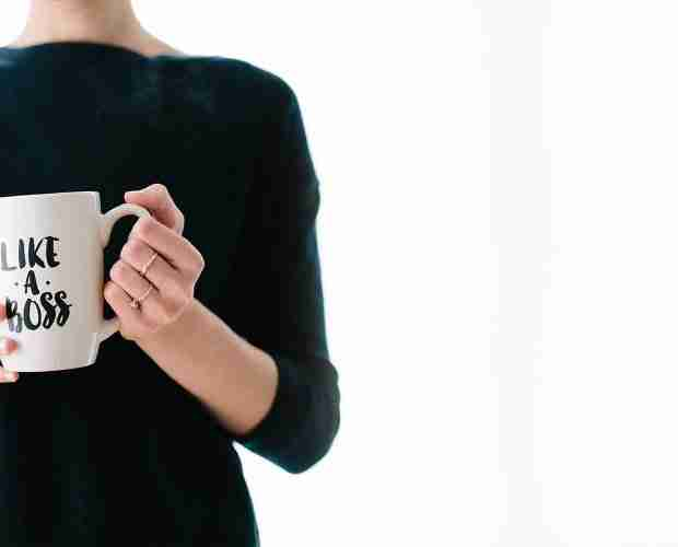 "A picture of a lady wearing a black top, standing against a white background, and holding a white coffee mug saying ""like a boss""."